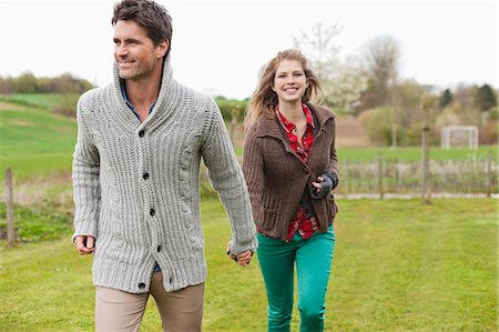 Couple holding hands in a field Stock Photo - Premium Royalty-Free, Code: 6108-06167351