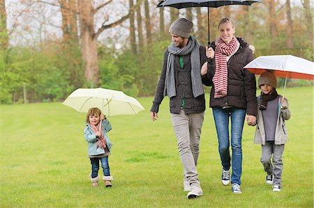 family shoes - Family walking with umbrellas in a park Stock Photo - Premium Royalty-Free, Code: 6108-06167366
