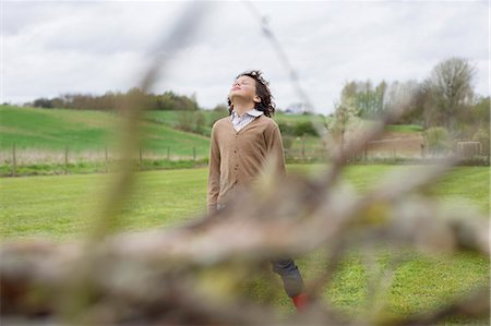 Boy daydreaming in a field Stock Photo - Premium Royalty-Free, Code: 6108-06167373