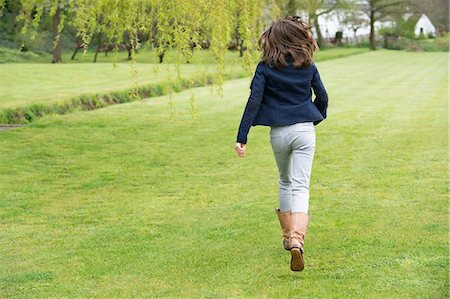 Girl running in a field Stock Photo - Premium Royalty-Free, Code: 6108-06167388