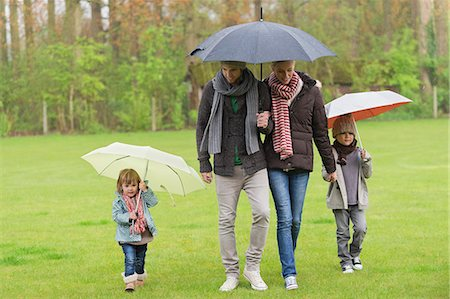 family shoes - Family walking with umbrellas in a park Stock Photo - Premium Royalty-Free, Code: 6108-06167389