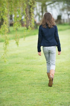 Girl walking in a field Stock Photo - Premium Royalty-Free, Code: 6108-06167397