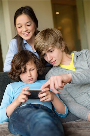 Boy using a cellphone with his brother and sister at home Stock Photo - Premium Royalty-Free, Code: 6108-06167313