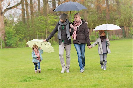 people with umbrellas in the rain - Family walking with umbrellas in a park Stock Photo - Premium Royalty-Free, Code: 6108-06167317