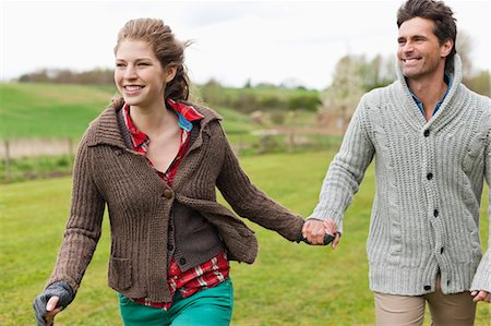 sweater - Couple holding hands in a field Stock Photo - Premium Royalty-Free, Code: 6108-06167315