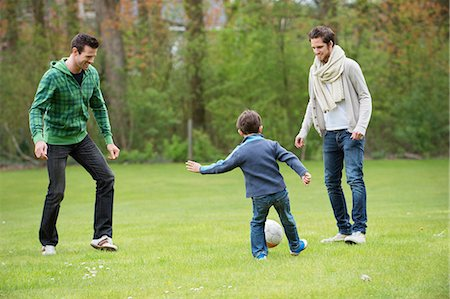Boy playing soccer with two men in a park Stock Photo - Premium Royalty-Free, Code: 6108-06167323
