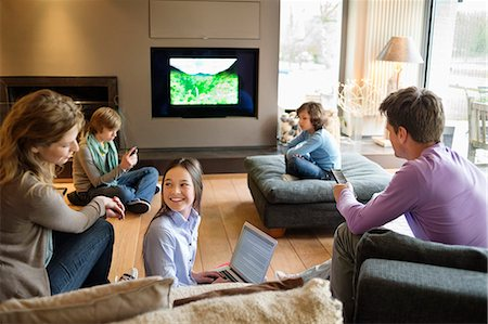 Family using electronic gadgets in a living room Stock Photo - Premium Royalty-Free, Code: 6108-06167467