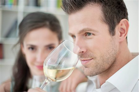 smelling - Man drinking white wine with his wife in the background Stock Photo - Premium Royalty-Free, Code: 6108-06167413