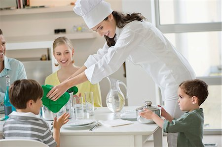 Little boy assisting his mother in serving dinner Stock Photo - Premium Royalty-Free, Code: 6108-06167411