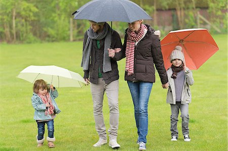 people with umbrellas in the rain - Family with umbrellas in a park Stock Photo - Premium Royalty-Free, Code: 6108-06167542