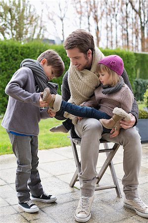 family shoes - Boy putting shoe on his sister sitting in her father's lap Stock Photo - Premium Royalty-Free, Code: 6108-06167545
