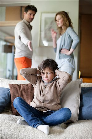 sad child sitting - Boy covering ears with hands while his parents arguing in the background Stock Photo - Premium Royalty-Free, Code: 6108-06167546
