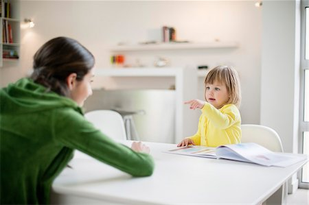 studying (all students) - Woman teaching her daughter at home Stock Photo - Premium Royalty-Free, Code: 6108-06167550