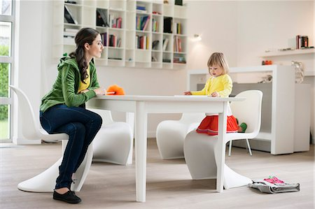 Woman teaching her daughter at home Stock Photo - Premium Royalty-Free, Code: 6108-06167561