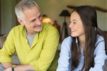 preteen girl - Man and his daughter smiling at home Stock Photo - Premium Royalty-Free, Code: 6108-06167511