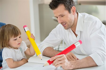 draw - Man and daughter writing with big pencils Stock Photo - Premium Royalty-Free, Code: 6108-06167601