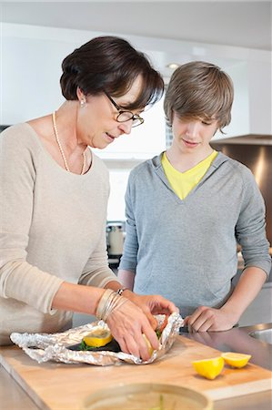 Elderly woman preparing seafood with her grandson in a kitchen Stock Photo - Premium Royalty-Free, Code: 6108-06167630