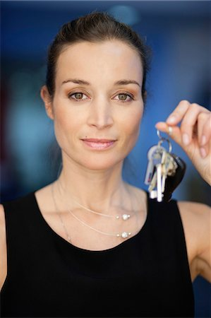 Portrait of a businesswoman holding keys Stock Photo - Premium Royalty-Free, Code: 6108-06167795