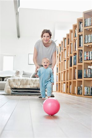 floor - Woman playing with her daughter walking towards a ball Stock Photo - Premium Royalty-Free, Code: 6108-06167723