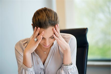 Close-up of a businesswoman suffering from a headache in an office Stock Photo - Premium Royalty-Free, Code: 6108-06167843