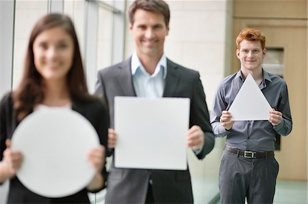 person holding sign - Business executives holding geometrical shaped placards in an office Stock Photo - Premium Royalty-Free, Code: 6108-06167867