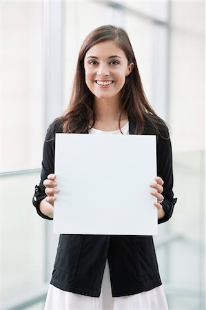 Portrait of a businesswoman holding a blank placard and smiling in an office Stock Photo - Premium Royalty-Free, Code: 6108-06167869