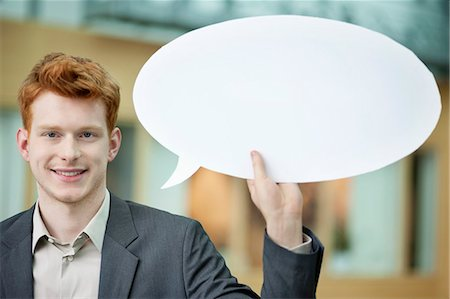 Businessman holding a speech bubble and smiling in an office Stock Photo - Premium Royalty-Free, Code: 6108-06167871