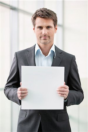 sign - Businessman holding a blank placard in an office Stock Photo - Premium Royalty-Free, Code: 6108-06167880