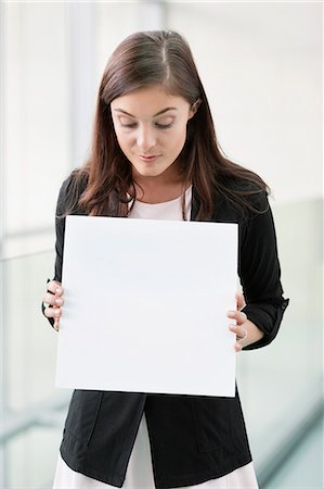 sign - Businesswoman holding a blank placard in an office Stock Photo - Premium Royalty-Free, Code: 6108-06167884