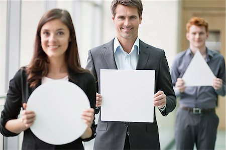 person holding sign - Business executives holding geometrical shaped placards in an office Stock Photo - Premium Royalty-Free, Code: 6108-06167886