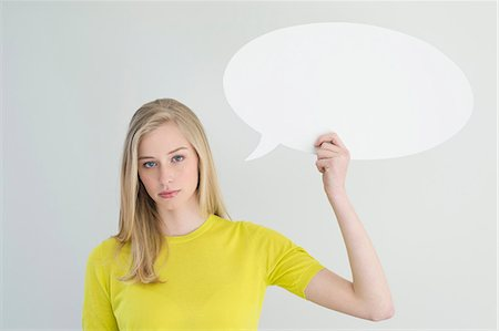 Serious woman holding a speech bubble Stock Photo - Premium Royalty-Free, Code: 6108-06167888