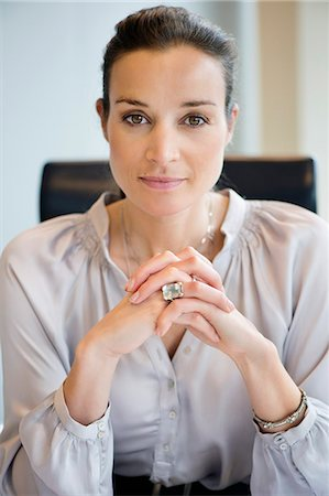 Portrait of a businesswoman with her hands clasped in an office Stock Photo - Premium Royalty-Free, Code: 6108-06167821