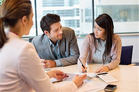 Couple signing documents with real estate agent Stock Photo - Premium Royalty-Free, Code: 6108-06167949