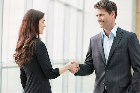 Business executives shaking hands in an office Stock Photo - Premium Royalty-Free, Code: 6108-06167955