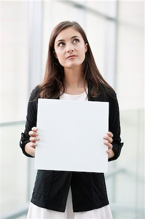 Businesswoman holding a blank placard and thinking in an office Stock Photo - Premium Royalty-Free, Code: 6108-06167900
