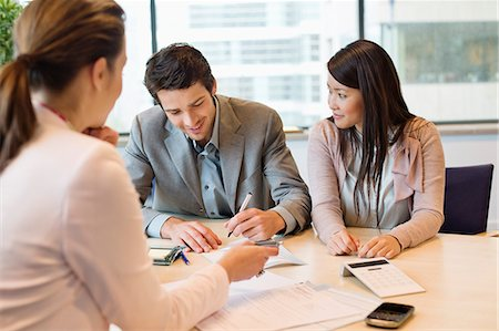 Couple signing documents with business executive Stock Photo - Premium Royalty-Free, Code: 6108-06167913