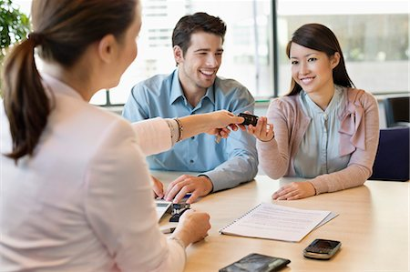 Couple receiving keys from business executive Stock Photo - Premium Royalty-Free, Code: 6108-06167915