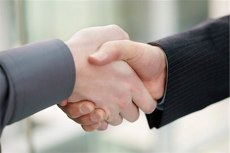 Close-up of businessmen shaking hands in an office Stock Photo - Premium Royalty-Free, Code: 6108-06167934