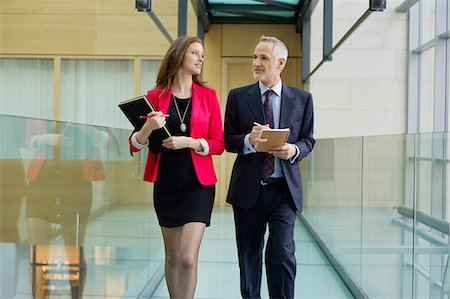 Business executives discussing in an office corridor Stock Photo - Premium Royalty-Free, Code: 6108-06168042