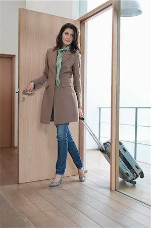 Woman arriving at home from vacations Stock Photo - Premium Royalty-Free, Code: 6108-06168048