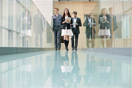 Business executives walking in a corridor Stock Photo - Premium Royalty-Free, Code: 6108-06168059