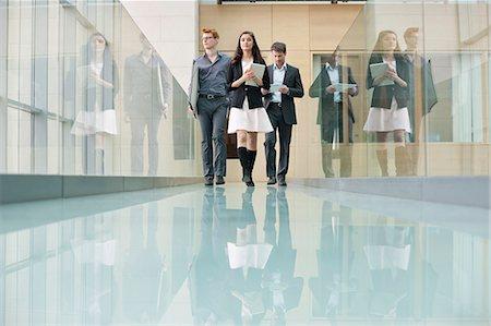 Business executives walking in a corridor Stock Photo - Premium Royalty-Free, Code: 6108-06168059