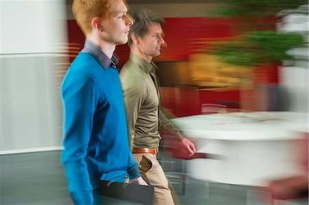 Businessmen walking in an office corridor Stock Photo - Premium Royalty-Free, Code: 6108-06168093