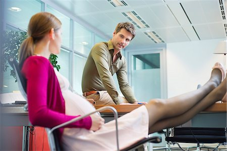 Pregnant woman talking to her colleague in the office Stock Photo - Premium Royalty-Free, Code: 6108-06168018