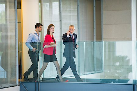 Business executives walking in an office corridor Stock Photo - Premium Royalty-Free, Code: 6108-06168021