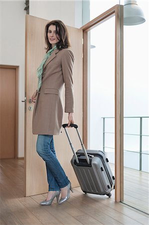Woman arriving at home from vacations Stock Photo - Premium Royalty-Free, Code: 6108-06168033