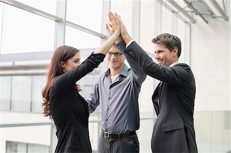 Business executives giving high-five to each other Stock Photo - Premium Royalty-Free, Code: 6108-06168160
