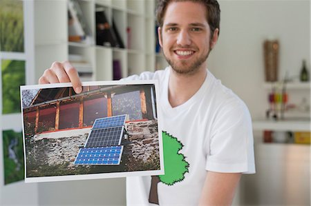 Man showing an ecological poster of solar panel Foto de stock - Royalty Free Premium, Número: 6108-06168107