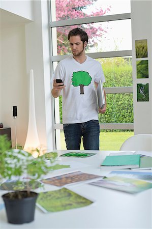 poster - Man using a mobile phone with environment related posters in front of him on a table Stock Photo - Premium Royalty-Free, Code: 6108-06168125