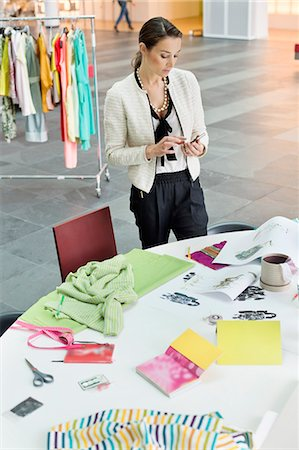 Female fashion designer text messaging in an office Stock Photo - Premium Royalty-Free, Code: 6108-06168267
